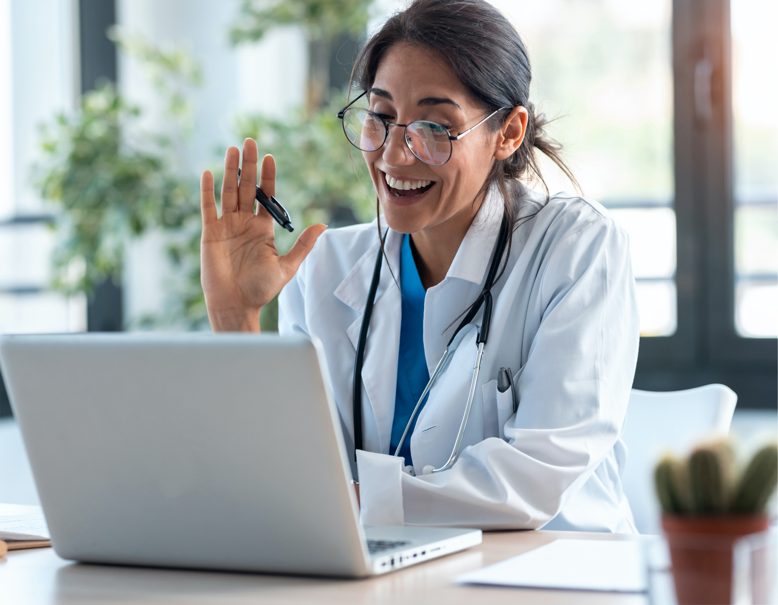 Maven Project, doctor smiles at her computer on a video chat